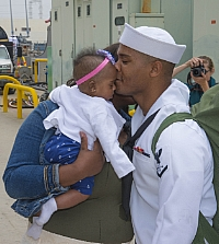140417-N-SU278-076 SAN DIEGO (April 17, 2014) A Sailor assigned to the guided-missile cruiser USS Cowpens (CG 63) kisses his baby for the first time during a homecoming celebration at Naval Base San Diego. Cowpens played a critical role in Operation Damayan, a joint service humanitarian assistance and disaster recovery mission following Super Typhoon Haiyan in the Republic of the Philippines. (U.S. Navy photo by Mass Communication Specialist 3rd Class Will Gaskill/Released)